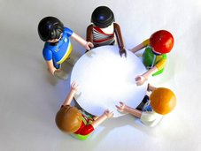 A group of toy people gathered around a table